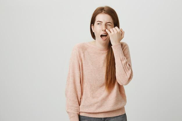 Głupia ruda dziewczyna dłubie w nosie i patrzy na bok