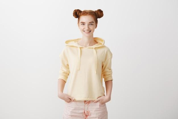 Głupia ruda nastolatka z śmieszną fryzurą, uśmiechając się