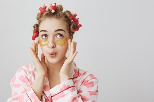 Głupia śliczna dziewczyna w lokówkach i piżamie nakłada opaski na oczy