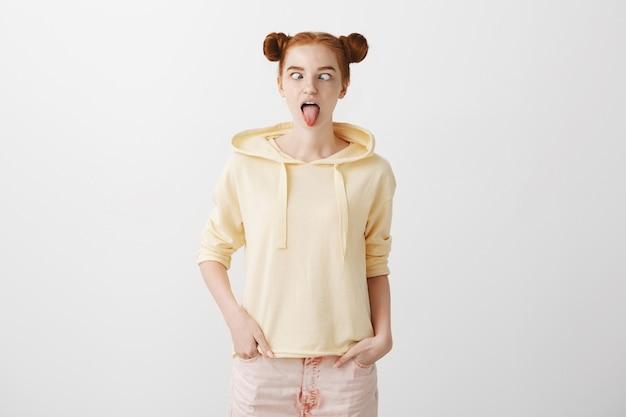 Głupia śmieszna ruda dziewczyna pokazuje język i mruży oczy