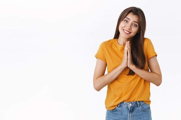 Głupia, uśmiechnięta, lepka dziewczyna z anielskim wyrazem twarzy, trzymająca się za ręce w modlitwie, przechylająca głowę i zalotnie wpatrująca się w kamerę, błagająca o przysługę, pożyczająca pieniądze od przyjaciela, prosząca o radę, przepraszająca, białe tło