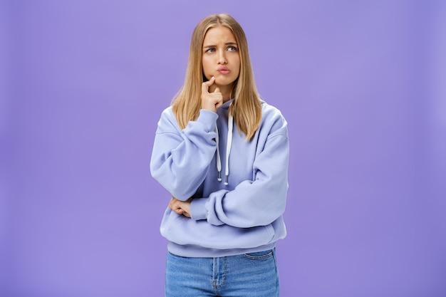 Głupia zatroskana dziewczyna próbuje wymyślić, jak rozwiązać problem stojąc zamyślona ze zmartwioną miną dotykając wydymanej szczęki, marszczącej brwi, wpatrującej się w prawo, zastanawiającej się nad podjęciem decyzji nad fioletową ścianą
