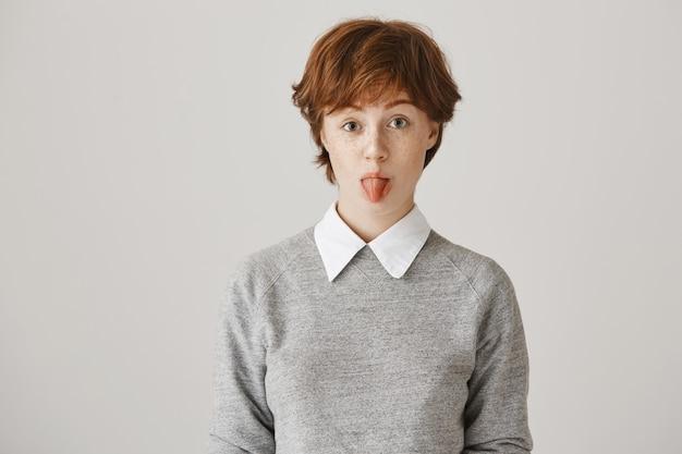 Głupiutka ruda dziewczyna z krótką fryzurą, pozowanie na białej ścianie