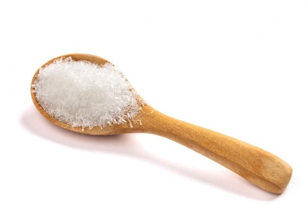 Glutaminian monosodowy, msg na drewnianej łyżce odizolowywającej na białym tle