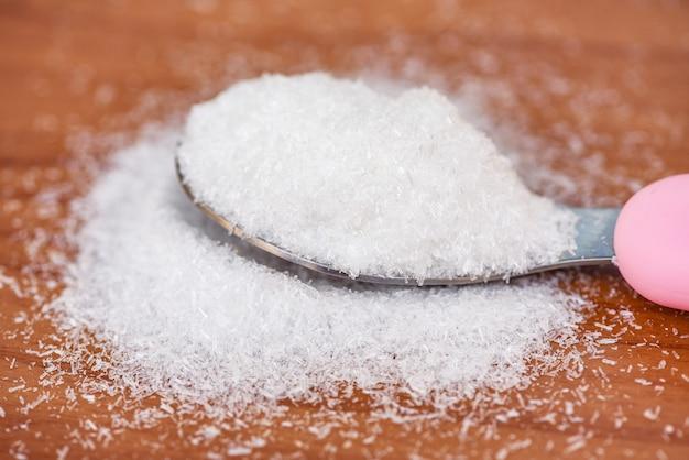 Glutaminian sodu na tle łyżka i drewniany stół, glutaminian sodu do przyprawiania żywności