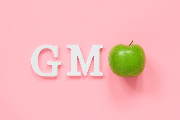 Gmo tex z białych liter objętości i zielonego jabłka na różowym tle. pojęcie genetycznie zmodyfikowanej żywności lub owoców