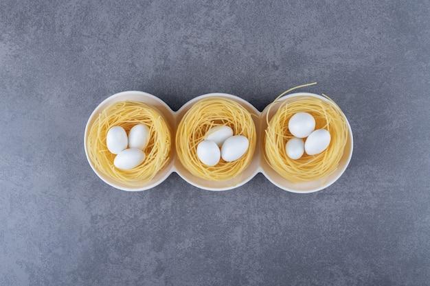 Gniazda makaronu jajecznego z białymi cukierkami w miseczkach.