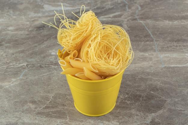 Gniazda niegotowanego makaronu i penne w żółtym wiaderku.