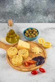 Gniazda spaghetti, warzywa i ser na desce z oliwkami.