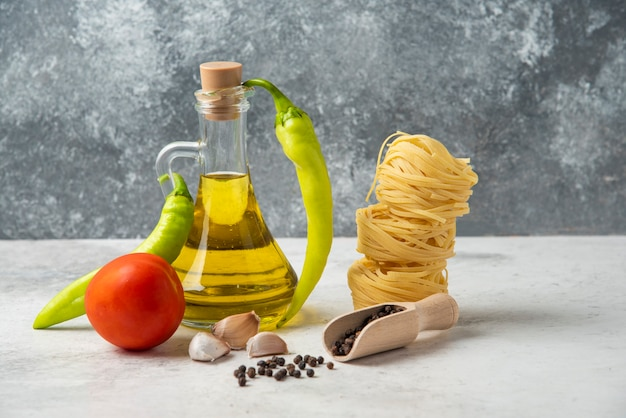 Gniazda surowego makaronu, butelka oliwy, ziarna pieprzu i warzywa na białym stole.