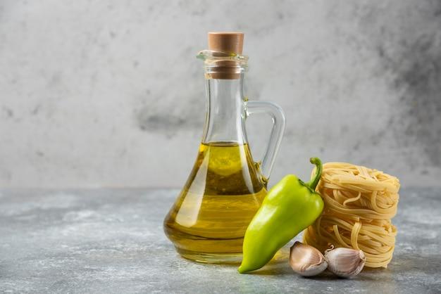 Gniazda surowego makaronu tagliatelle, butelka oleju i warzywa na marmurowym tle.