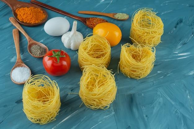 Gniazda surowego makaronu z przyprawami i warzywami na niebieskiej powierzchni.