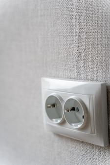 Gniazdko elektryczne w pokoju po przebudowie procesu z szarą tapetą na ścianie dla miejsca kopiowania
