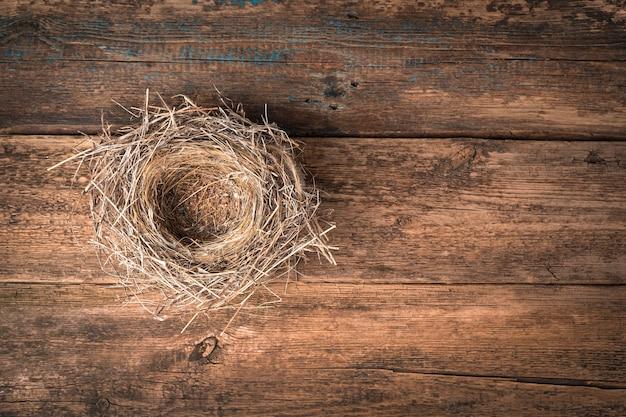 Gniazdo wykonane z suchej trawy na naturalnym drewnianym tle. widok z góry, poziomy, z miejscem do skopiowania.