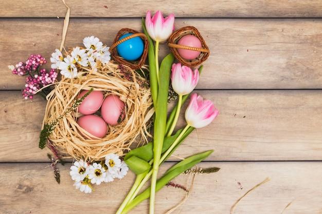 Gniazdo z różowymi jajkami w pobliżu tulipanów