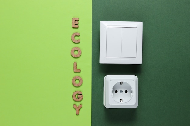 Gniazdo zasilania i przełącznik z napisem ekologia na zielonej powierzchni.