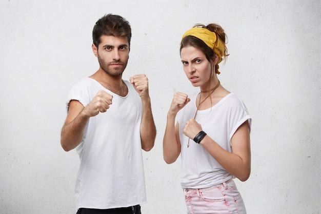 Gniewna, agresywna młoda para rasy kaukaskiej stojąca w pozycji obronnej, z zaciśniętymi pięściami, z pewnym siebie zdecydowanym wyglądem, gotowa do obrony i obrony swoich praw