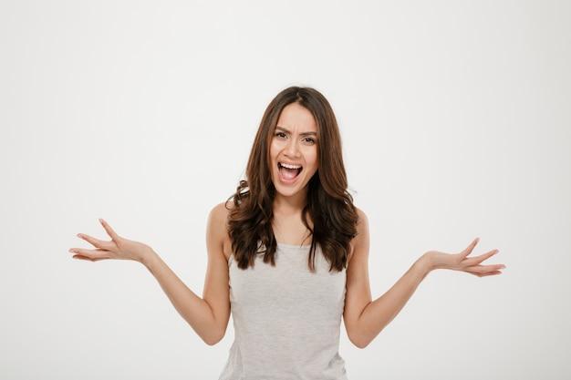 Gniewna brunetki kobieta krzyczy kamerę i patrzeje nad popielatym