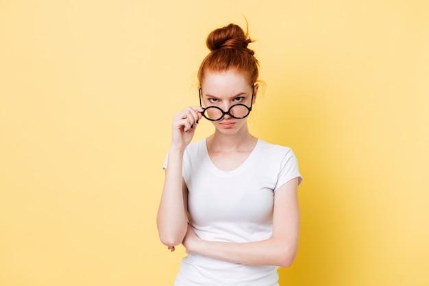 Gniewna imbirowa kobieta patrzeje przez okularów