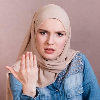 Gniewna islamska kobieta pokazuje ręka gest
