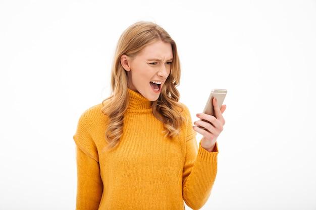Gniewna krzycząca młoda kobieta używa telefon komórkowego.