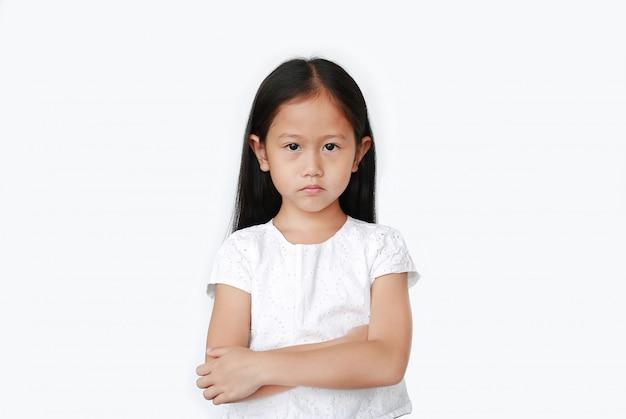 Gniewna mała dziewczynka pokazuje frustrację i nieporozumienie twarz z wyrazem twarzy skrzyżowane na białym