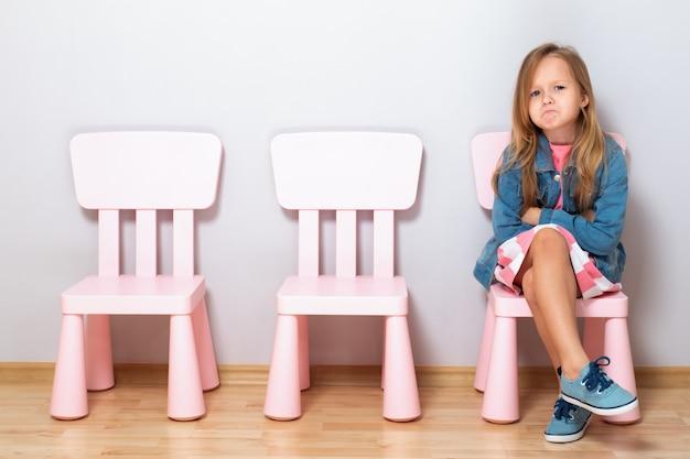 Gniewna mała dziewczynka siedzi na krześle.