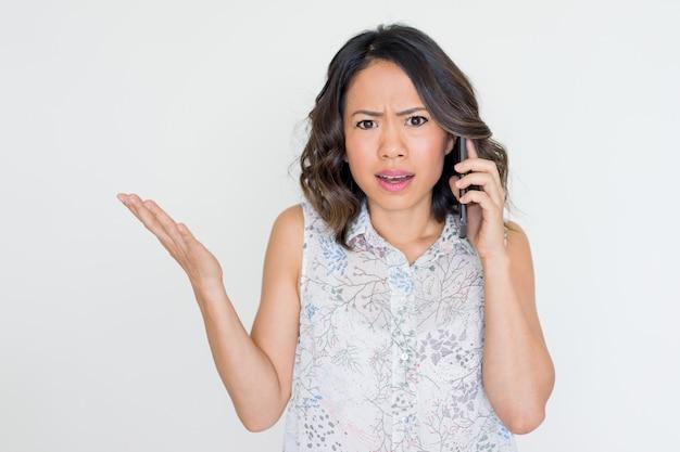 Gniewna młoda azjatycka dama opowiada na telefonie