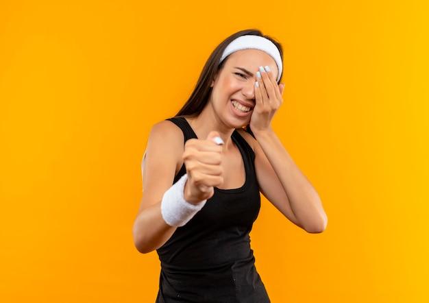 Gniewna młoda ładna sportowa dziewczyna nosi opaskę na głowę i nadgarstek, wyciągając pięść i kładąc rękę na oku cierpiącym na ból na pomarańczowej ścianie z kopią miejsca