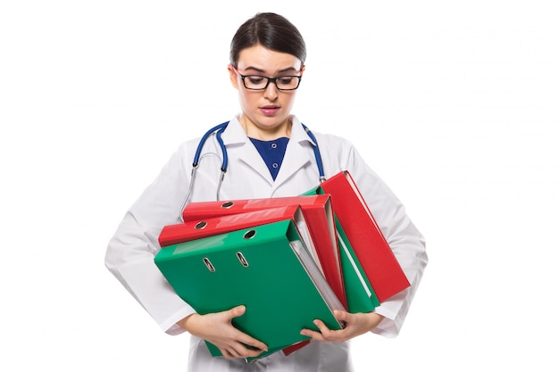 Gniewna młodej kobiety lekarka z stetoskopu mienia segregatorami w jej rękach w bielu mundurze na bielu