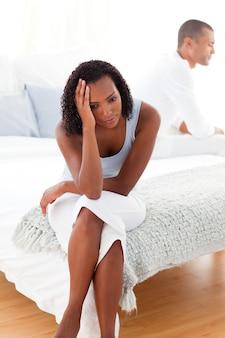 Gniewna para siedzi na łóżku oddzielnie