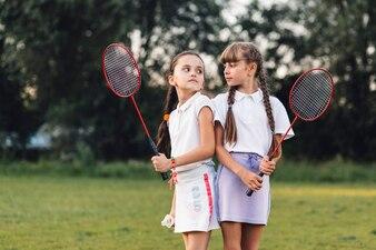 Gniewne dziewczyny trzyma badminton w ręce patrzeje each inny