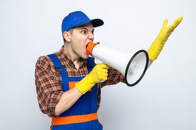 Gniewnie wyglądający młody facet sprzątający w mundurze i czapce z rękawiczkami mówi przez głośnik