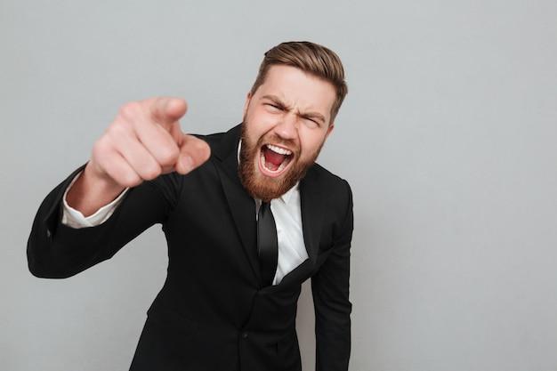 Gniewny biznesmen krzyczy palec i wskazuje w kostiumu