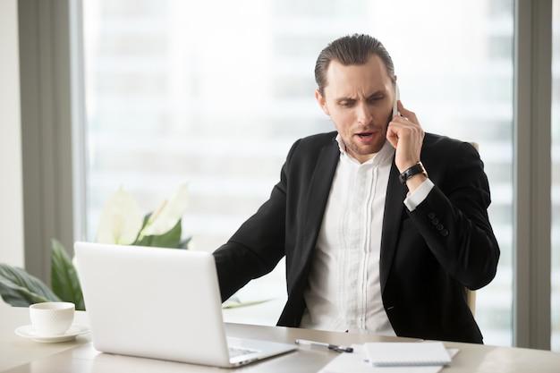 Gniewny biznesmen opowiada na telefonie komórkowym