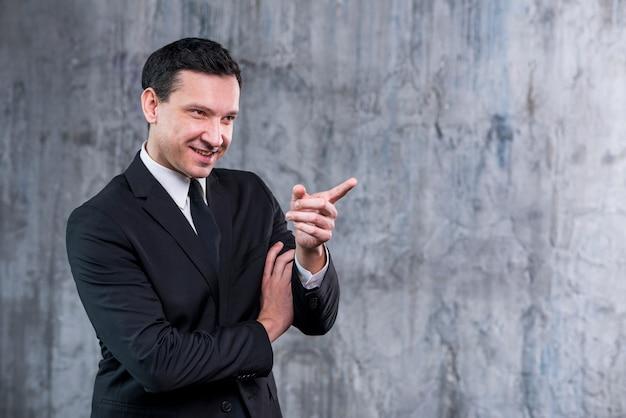 Gniewny biznesmen uśmiecha się szeroko i wskazuje
