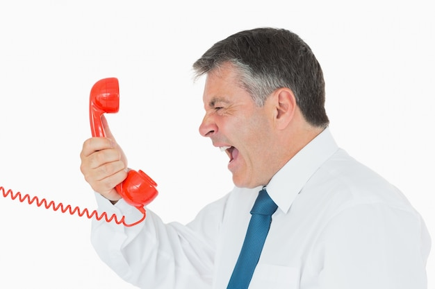 Gniewny biznesmen wrzeszczy przy telefonem