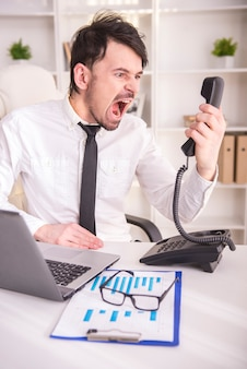 Gniewny biznesowy mężczyzna krzyczy przy telefonem w jego biurze