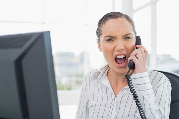 Gniewny bizneswoman krzyczy na telefonie podczas gdy patrzejący kamerę