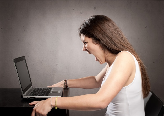 Gniewny bizneswoman pracuje z laptopem