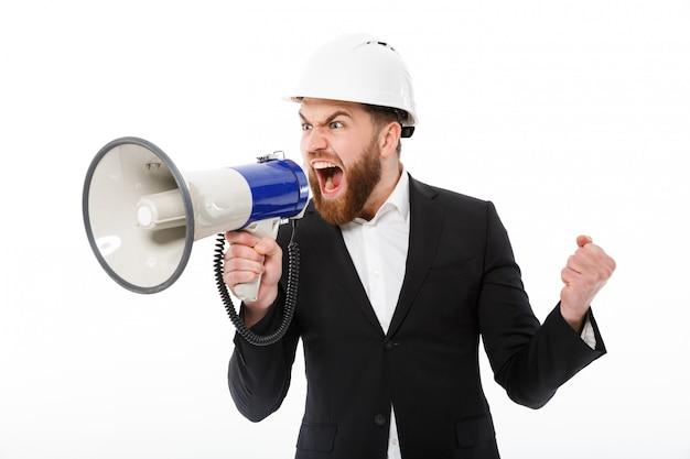 Gniewny brodaty mężczyzna krzyczy w megafonie w ochronnym hełmie