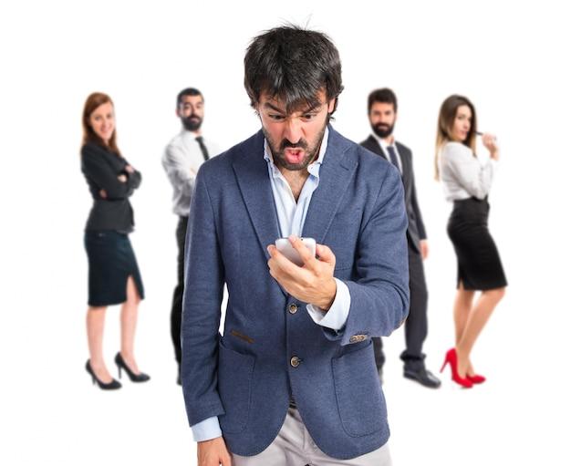 Gniewny człowiek rozmawia z telefonu komórkowego na białym tle