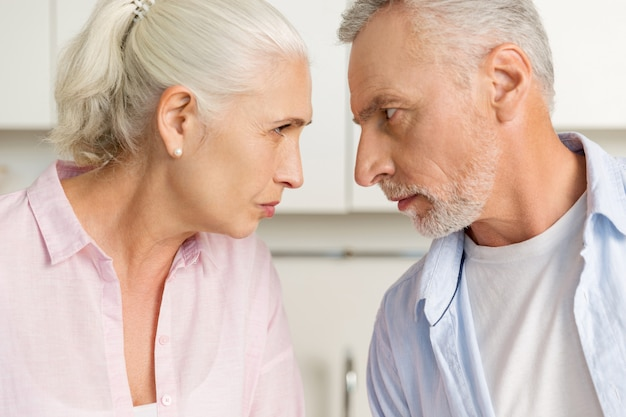 Gniewny dojrzały mężczyzna stoi blisko dojrzałej poważnej kobiety