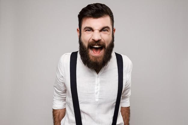 Gniewny grubiański młody przystojny mężczyzna krzyczy nad bielem.