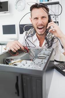 Gniewny inżynier komputerowy robi wezwaniu