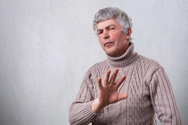 Gniewny marszczący brwi dojrzały mężczyzna ma negatywnego wyrażenie pokazuje odmawianie znaka z palmą