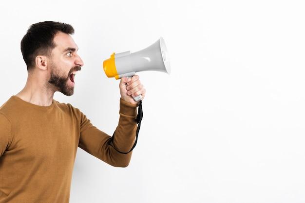 Gniewny mężczyzna krzyczy w megafonie