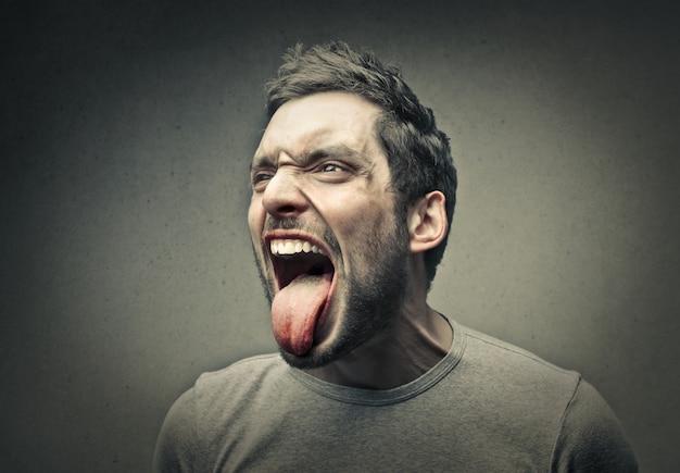 Gniewny mężczyzna pokazuje jego język
