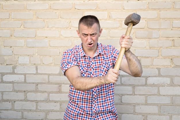 Gniewny mężczyzna z młotem na ściana z cegieł