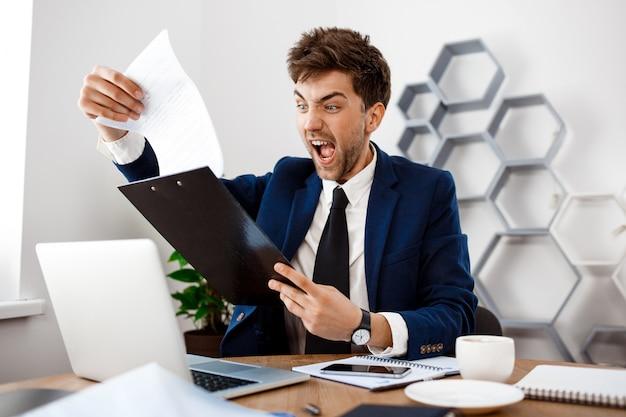 Gniewny młody biznesmena obsiadanie przy miejscem pracy, biurowy tło.